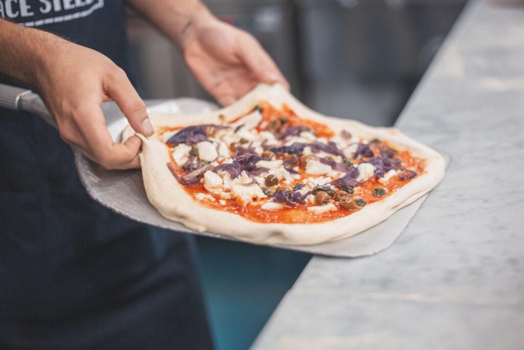 Pizza Tropeana con cipolla rossa caramellata, pomodoro, fiordilatte, olive taggiasche e capperi