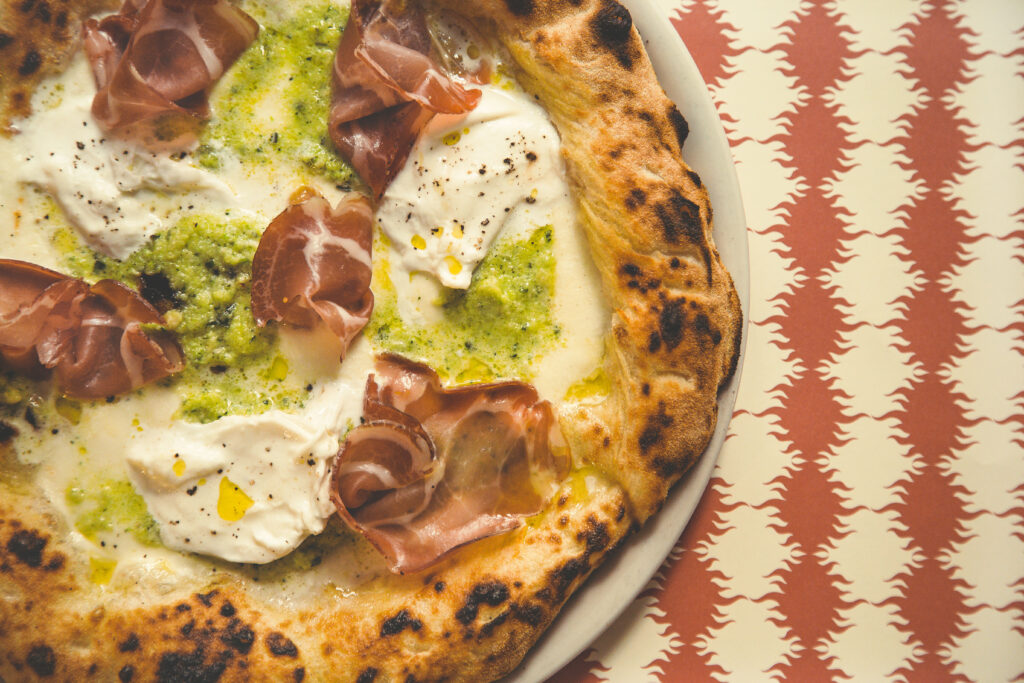 Pizze Regionali_i sapori del Sud_La Pugliese con Capocollo, burrata, pesto di zucchine con Mandorle su tovaglietta rossa di Fornace Stella